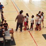 Árbitro, entrenadores y jugadores, chicos y chicas, al final del partido amistoso